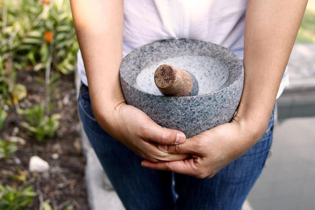 Una persona coge un mortero de piedra y madera